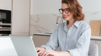 web_drobotdean_elegant-smiling-woman-in-glasses-and-striped-shirt-using-laptop-computer-while-siting-at-table-in-kitchen.jpg